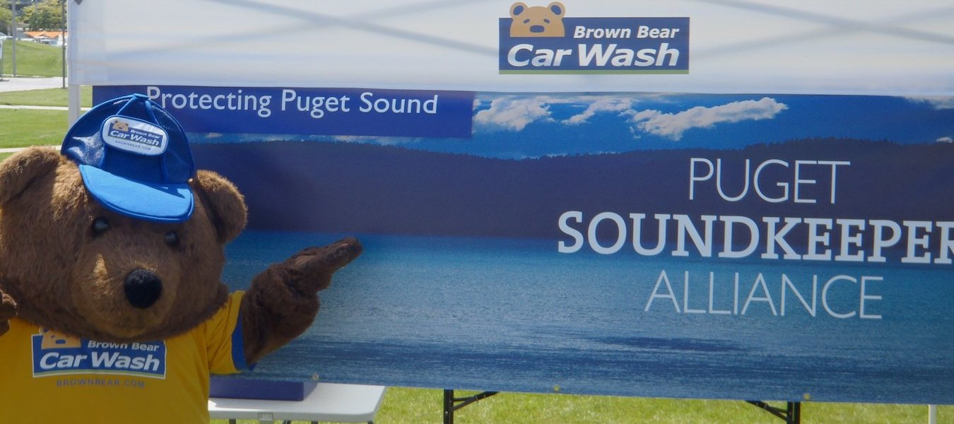 The Brown Bear Car Wash mascot stands in front of a tent at a Soundkeeper cleanup event sponsored by Brown Bear.