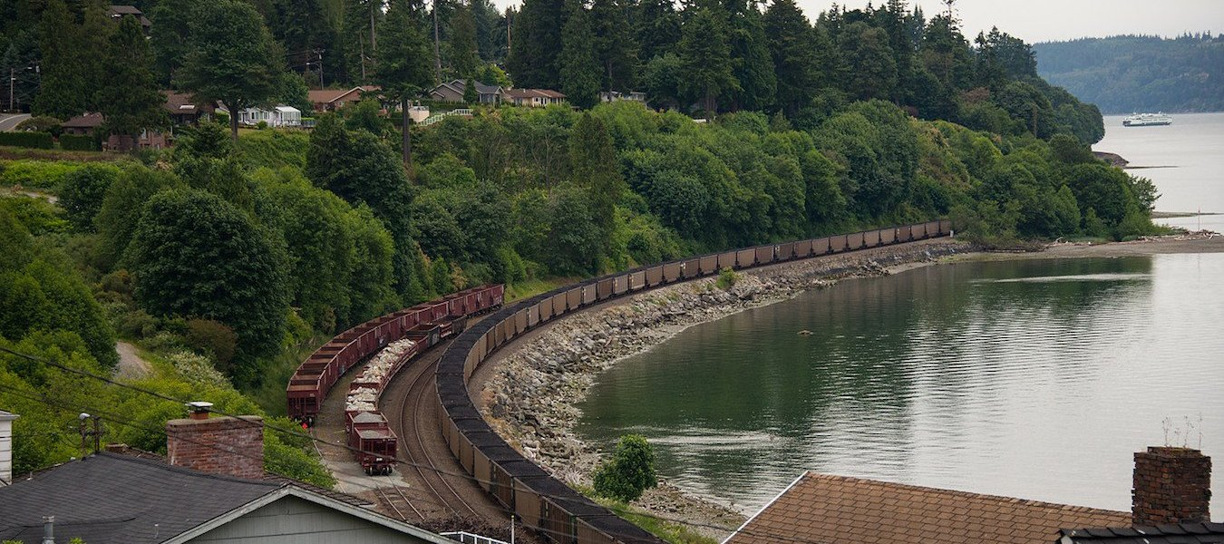 A coal train travels along the shoreline in Washington. Photo Paul K Anderson
