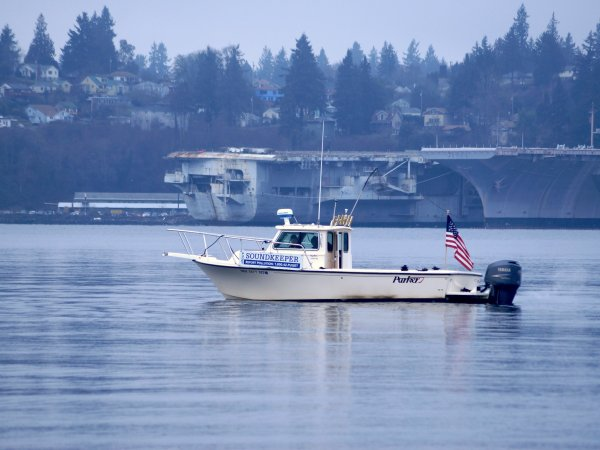 The Soundkeeper patrol boat passes in front of the decommissioned aircraft carrier at the naval shipyard in Bremerton.