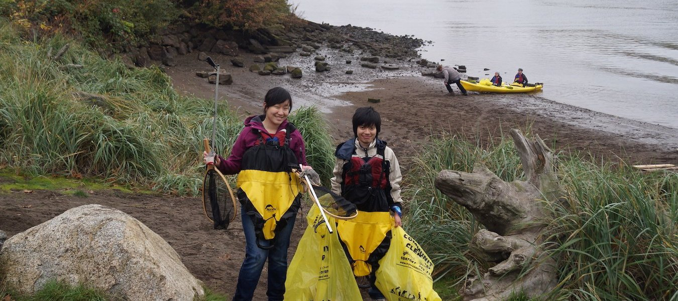 Volunteers stand with their trash bags in front of the Duwamish River after a community event, Duwamish Alive!, funded in part by the Puget Sound Stewardship and Mitigation Fund.
