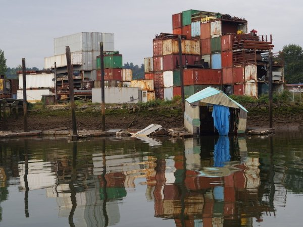 A sinking boathouse in front of stacks of cargo containers along the bank of the Duwamish River.