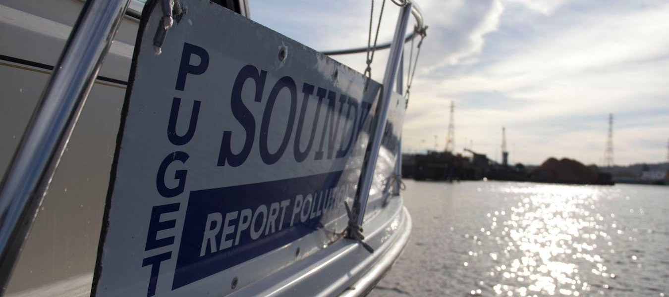 A view of the sign on the side of the Puget Soundkeeper boat, with the Duwamish River in the background.