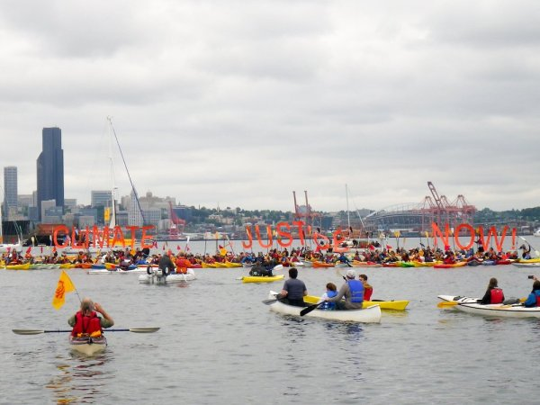 Kayakers at the Paddle In Seattle in 2015 hold a sign calling for Climate Justice Now in front of the Seattle waterfront.