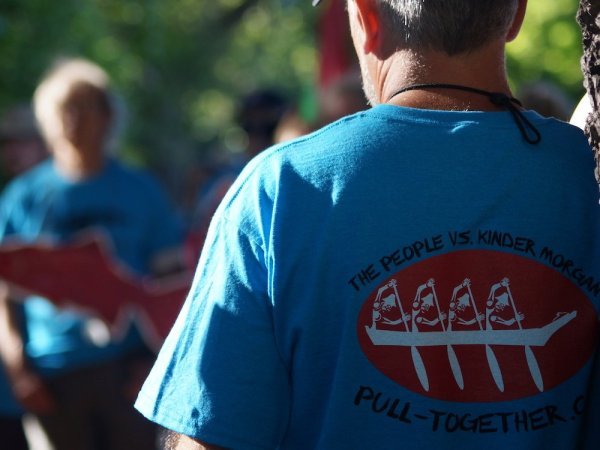 """A person's back is shown leaning against a tree. They are wearing a shirt with a logo of people paddling a canoe, and text """"The People vs. Kinder Morgan"""""""