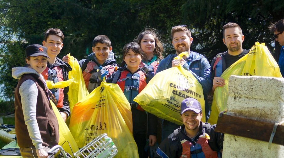 A group of volunteers pose with their trash bags after a Duwamish River cleanup.