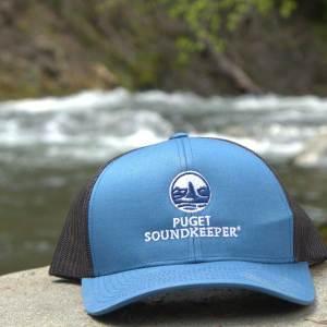 Blue Puget Soundkeeper hat on riverside rock