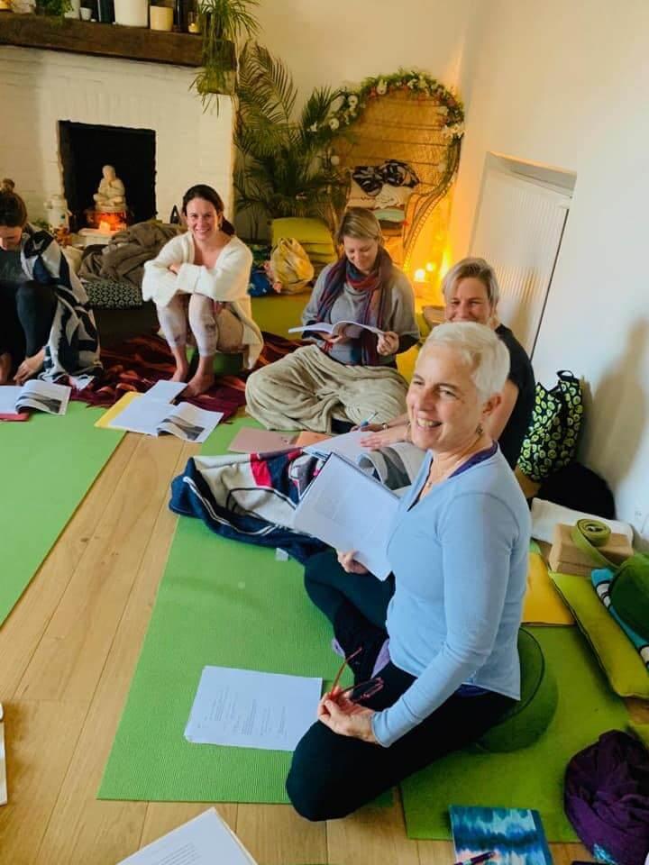 Profesora de yoga y sus alumnas en una sala con esterillas y accesorios de yoga sonríen en una formación de yoga donde están estudiando