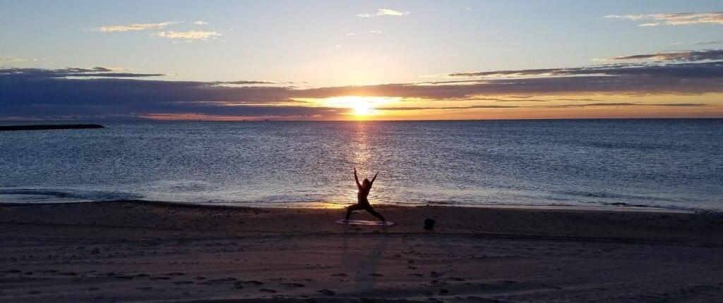 Sue Flamm haciendo una postura de yoga en la arena de la playa al borde del mar durante la salida del sol