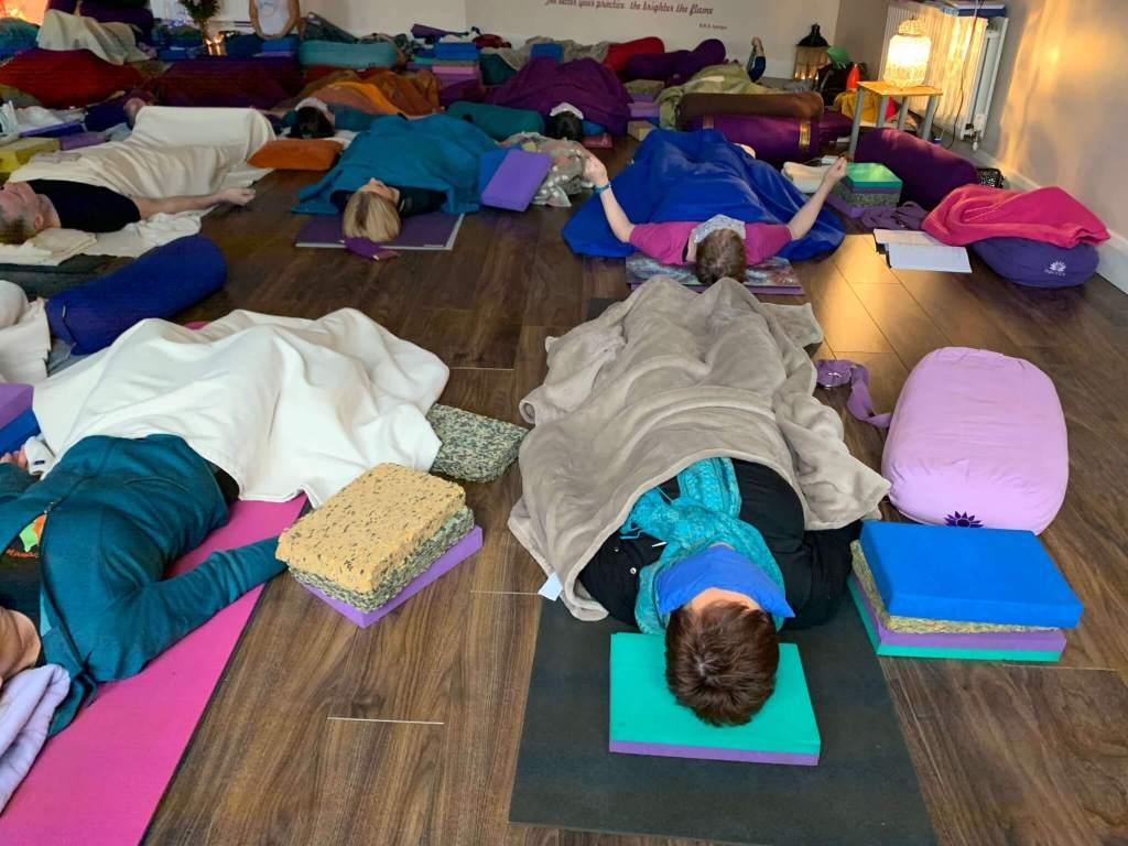 Alumnos de una clase de yoga restaurativo acostados sobre sus esterillas y tapados con mantas en sesión de relajación