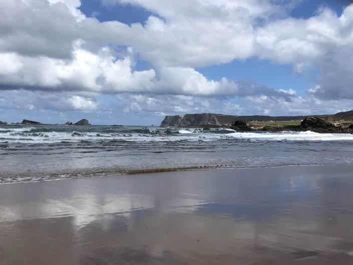 Paisaje en día nublado de una playa de arena oscura y montañas al fondo de Cantabria