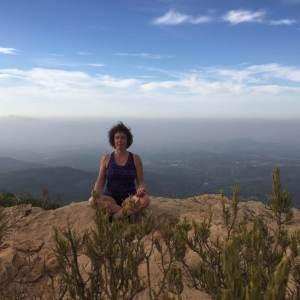 Sue Flamm meditando en lo alto de una montaña
