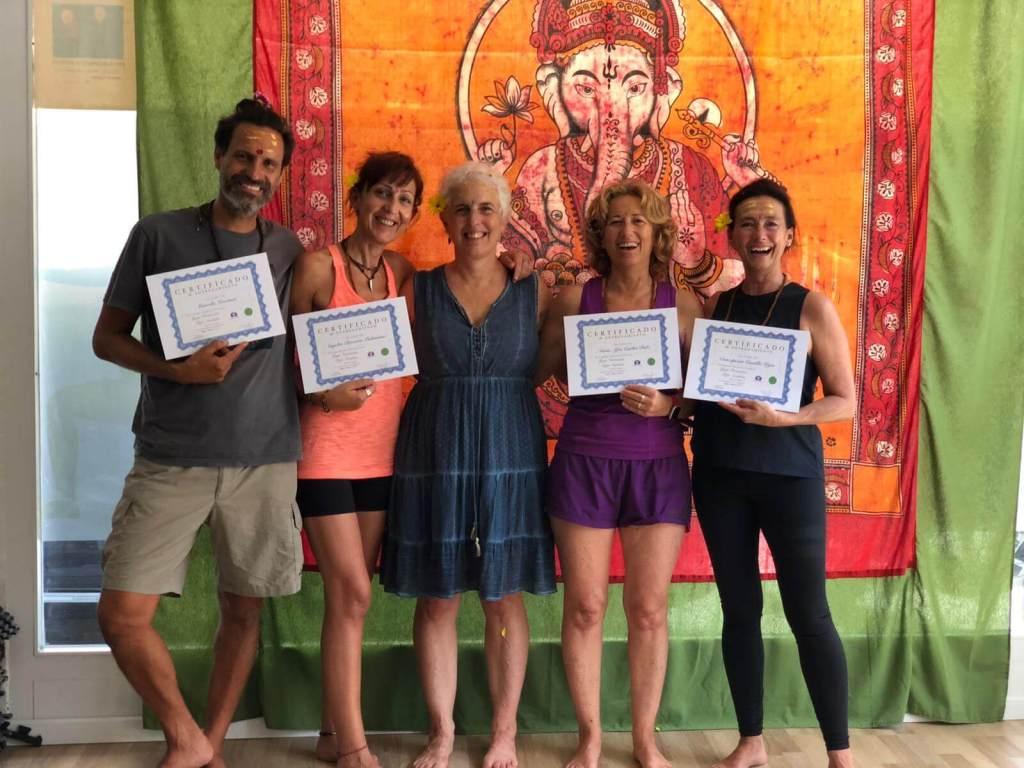 En una sala de yoga l profesora junto a los alumnos de una formación de yoga restaurativo que presentan en sus manos sus certificados del curso realizado