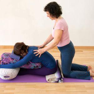Sala de yoga donde la profesora ayuda en la posición con las manos sobre la espalda de la alumna que sentada sobre la esterilla se inclina sobre sus piernas y se apoya en bolstes y otros accesorios