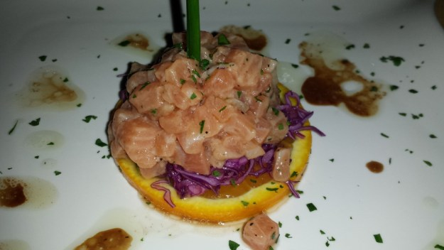 Atlantic Salmon tartare resting on an orange round