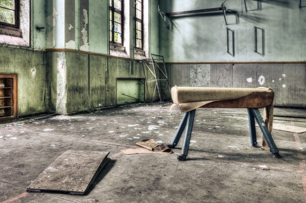 Dilapidated pommel horse in an abandoned school gymnasium
