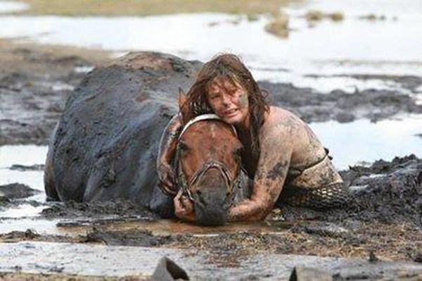 11. A woman helping a horse who got stuck in mud.