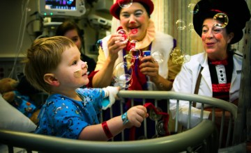 Victoria Millard, left, and Linda Severt, right, captivate patient Karsten Hendricks, 2, with music and bubbles (courtesy of John Curry Photography)
