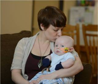 Rachel Dixon holds her son Ezra, who was born with severe combined immunodeficiency. SCID affects about 1 in every 50,000 babies born in the U.S. Nearly two months after having a life-saving bone marrow transplant from his brother, Judah, he's doing well. Photo courtesy of  Bo Jungmayer / Fred Hutch News Service