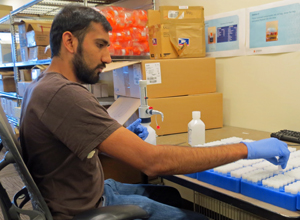 Rohit Nariya, research associate at GAPPS, adds preservative to hundreds of vials before they're added to the collection kits.