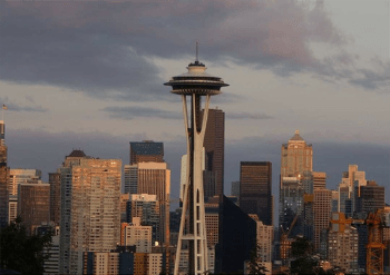 A photo showing the skyline of Seattle at dusk with some clouds in the sky.