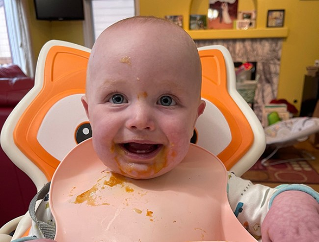 Photo of a baby smiling with food on his bib.