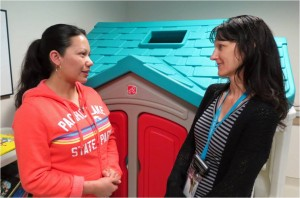 Social worker Yasha Carpentier (right) talks with a patient's mom about the Patient Emergency Assistance Fund.