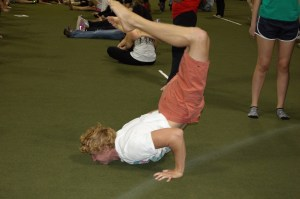 One student practices his scorpion pose before the start of Yoga World Record event, Tuesday, Oct. 14, 2014, in Cole Field House.