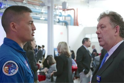 A young man wearing blue NASA coveralls speaks with a middle-aged man wearing a suit and tie.