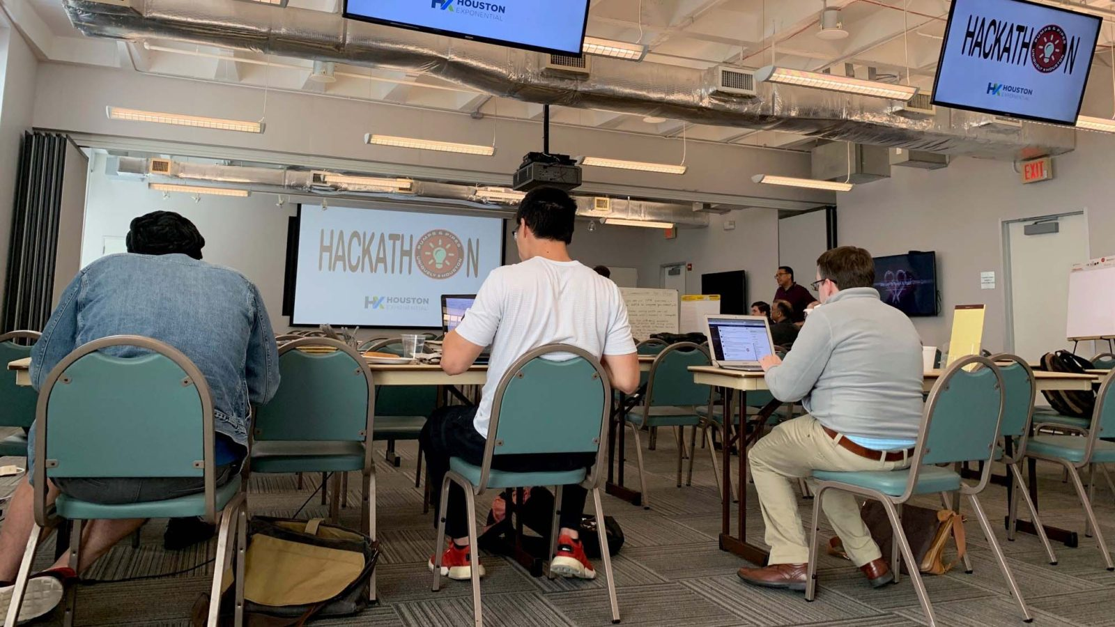 view from behind of three men sitting in chairs and working on laptops under Hackathon signs
