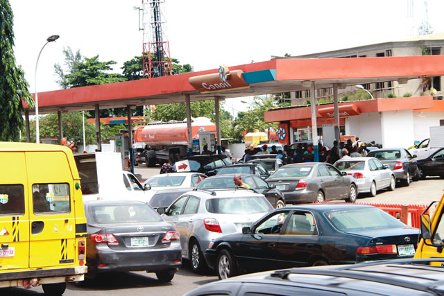 Image result for :People queueing at a fuel station, in Lagos .... last year. Photo: Saheed Olugbon