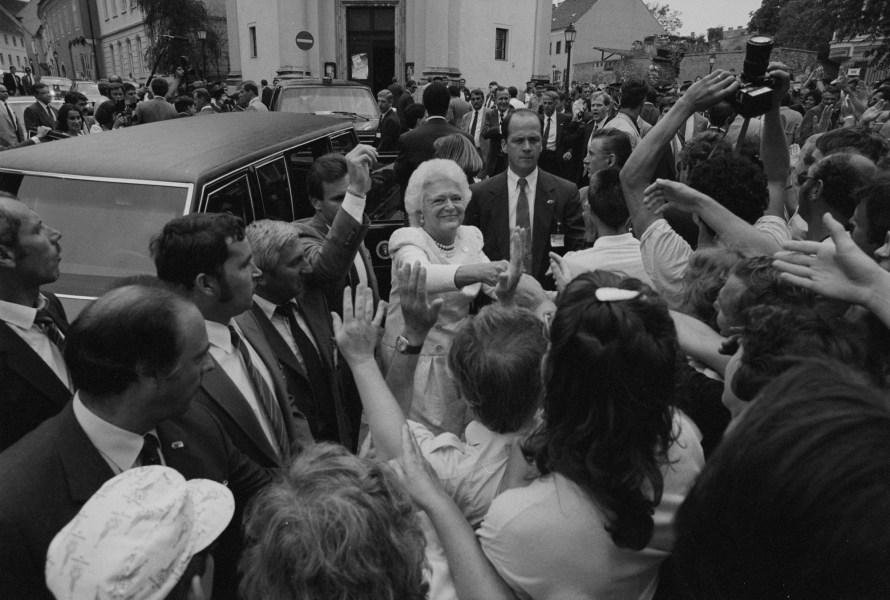 1989. július 13-án George H.W. Bush (1924-2018) az Egyesült Államok hivatalban lévő elnöke és felesége, Barbara Bush (1945-2018) a budai Bécsi kapu téren üdvözölték az ott lévőket. A First Lady az elnöki limuzinból történő kiszállás után rögtön a fotósokra nézett. © Fejér Zoltán