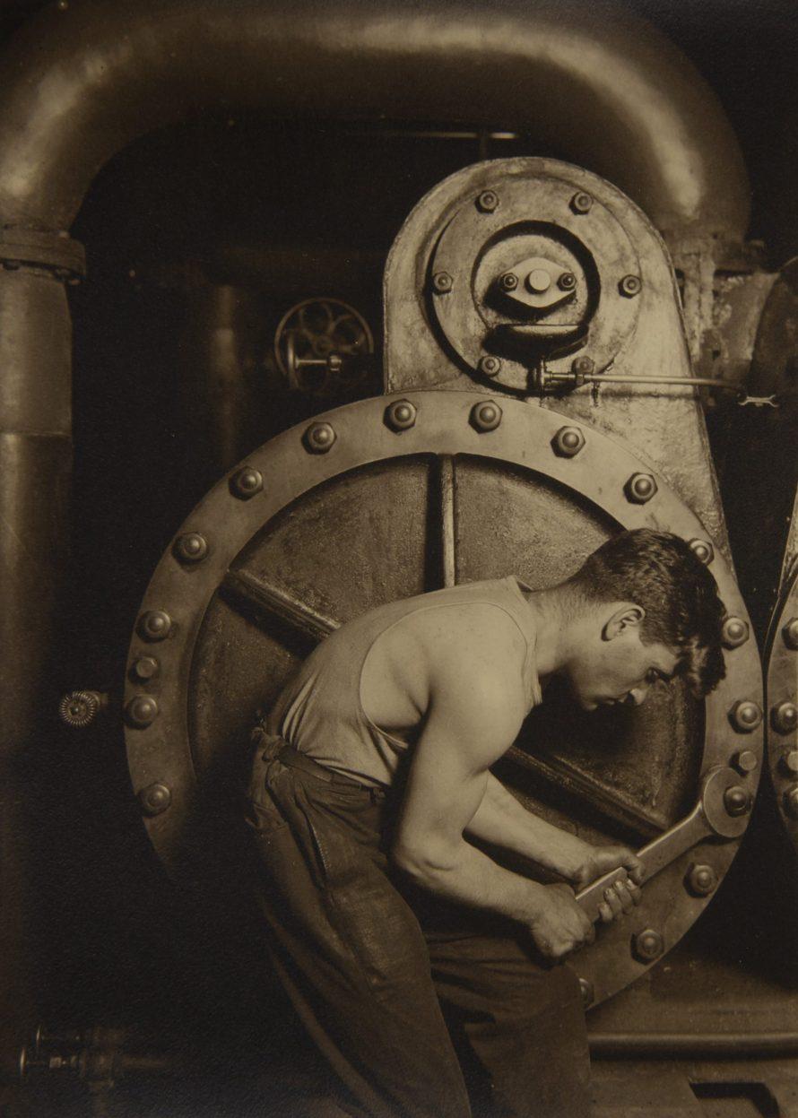 <b>LEWIS WICKES HINE (1874-1940)</b><br> <i>Mechanic and Steam Pump, 1921</i><br> gelatin silver print<br> image: 9 5/8 x 7 in. <br> sheet: 10 x 8 in.  <br> <b>Estimate:</b> $100,000-150,000