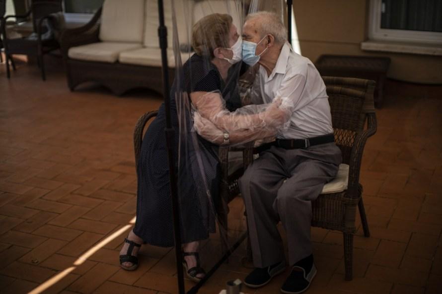 Fotó: <b>Emilio Morenatti</b>: A 81 éves Agustina Cañamero megöleli és megcsókolja férjét, Pascual Pérezt (84) egy műanyag vásznon keresztül, hogy elkerülje a koronavírus megfertőződését egy barcelonai idősek otthonában, 2020. június 22-én.