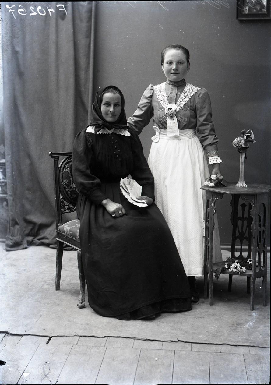 Fotó: Asszony hagyományos békési viseletben, lány polgári öltözékben. Az asszony kezében férje vagy fia frontról küldött levelei Békés, 1910-es évek második fele<br> Horváth Viktor felvétele Néprajzi Múzeum, F 40267