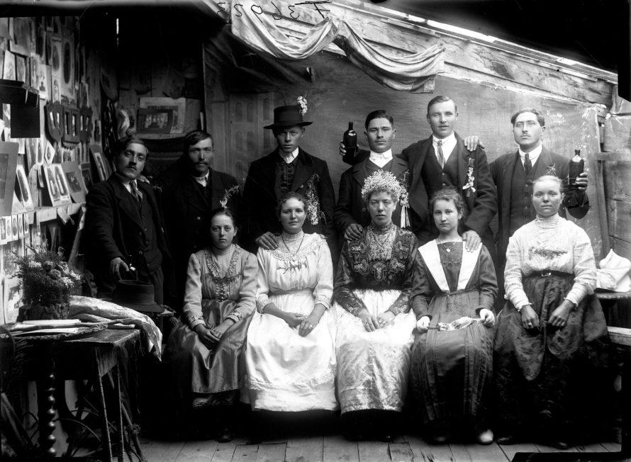 """Fotó: Esküvői csoportkép. Jól látszik műteremi kínálatot bemutató falrész (""""kirakat""""), illetve a helyiség szűkössége Szolnok, 1910-es évek<br> Papszt Piroska felvétele Néprajzi Múzeum, F 36923"""