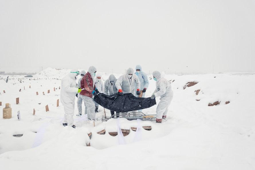 A Covid-19 áldozatának temetése, akit havas időben temettek el az iráni Wadi-Rahmat temetőben védőfelszerelésbe öltözött emberek. Betartva az egészségügyi protokollokat. Fotó: © Mehrdad Vahed Yousefabad
