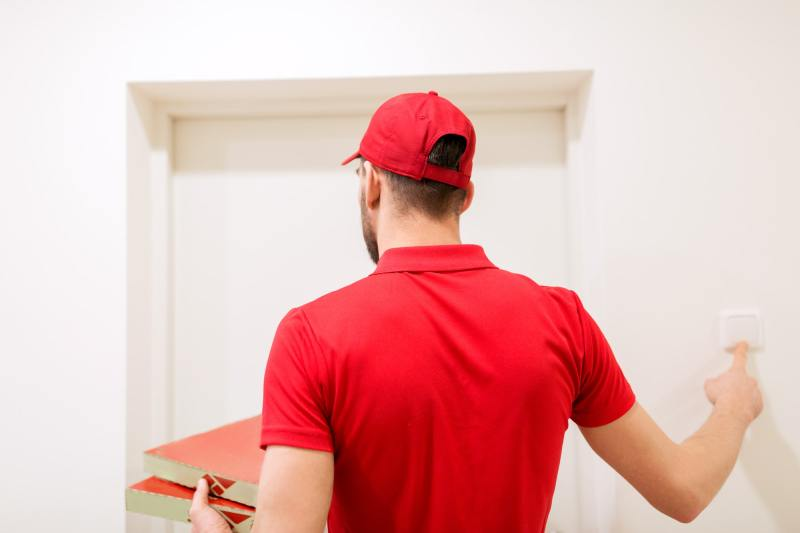 delivery man with pizza boxes ringing doorbell