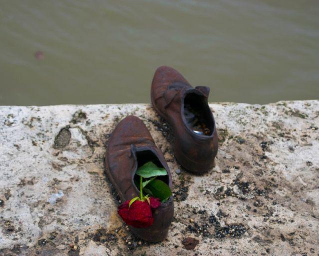 scarpre della memoria in ferro lungo il danubio con una rosa rossa all'interno