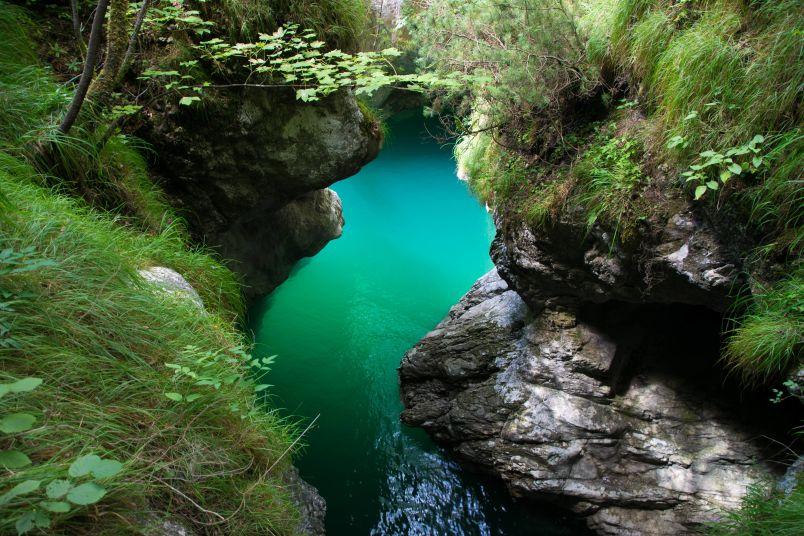 anfratto di roccia con riflesso dell'acqua del lago nel lago del mis e i dintorni