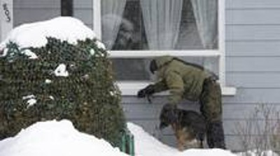 A police officer and his dog look for evidence near a home in the area of a Quebec City mosque on Monday January 30, 2017. A shooting at a Quebec City mosque left six people dead and eight others injured Sunday. (Paul Chiasson/The Canadian Press)