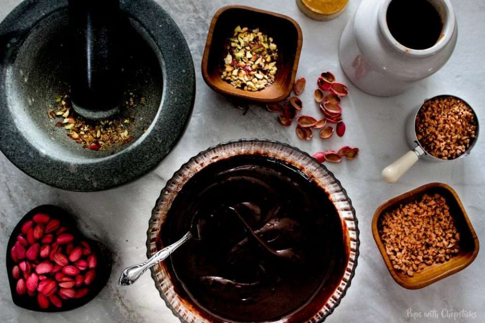 Melting chocolate and crushing pistachios for the Toffee Orange Chocolate Truffles