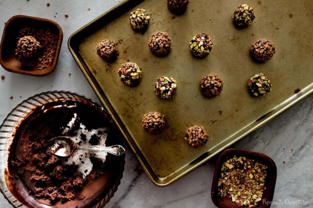Rolling chocolate into truffle balls and placing it on the tray