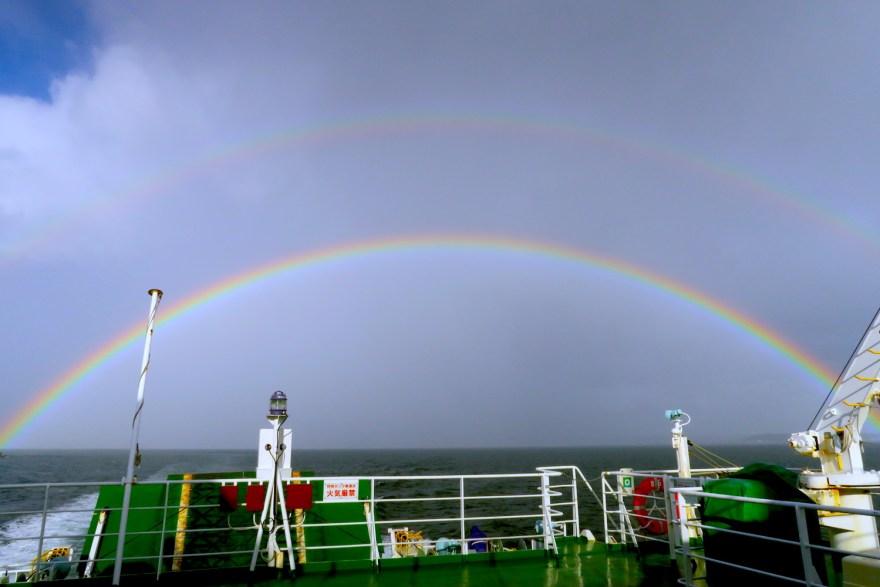 海にかかる幸せの二重の虹の写真