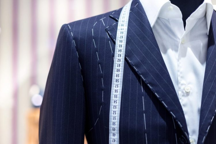 Navy blue men's suit with tailor's stitching and tape measure on a mannequin, symbolising bespoke services.