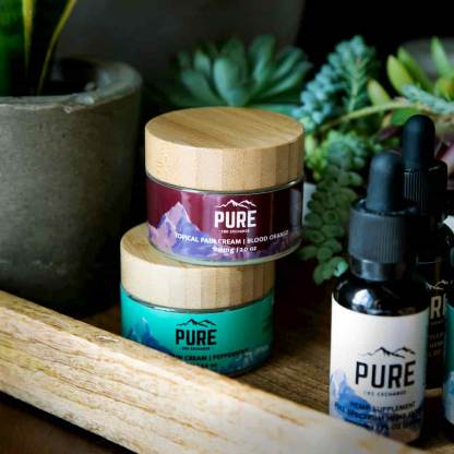 CBD Lotions stacked together next to some CBD tinctures