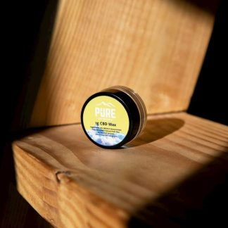 A tiny jar of CBD Wax Concentrate sitting by itself on a wooden bench