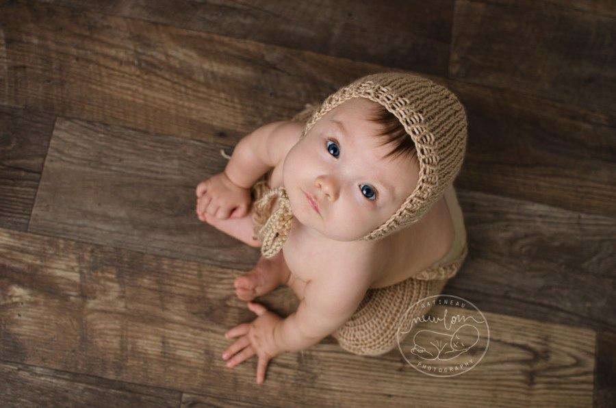 Baby Amelia 6-8 months milestone studio portrait barnwood floor knit short pant set bonnet smiling big blue eyes
