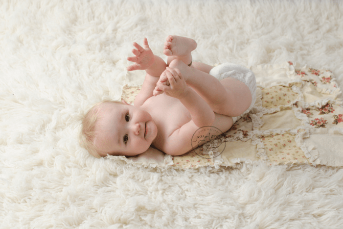 12-months-baby-photos-flokati-laying-down-back-rag-quilt-diaper-holding-feet