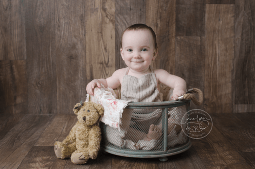 baby-photos-milestone-10-months-smiling-sitting-barnwood-floor-upcycled-sweater-sitter-romper-rag-quilt-antique-teddy-bear-mesh-bucket