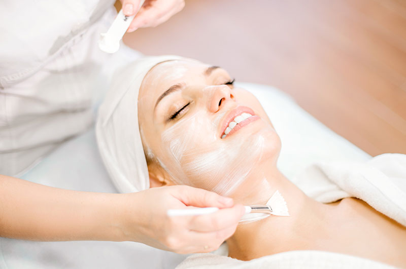 Cosmetology. The hands of a cosmetologist apply a cleansing face mask with a brush. Facial rejuvenation procedure.